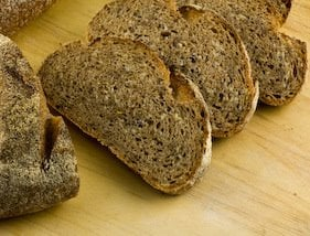 Slices of wheat and lentil bread on a wooden work surface