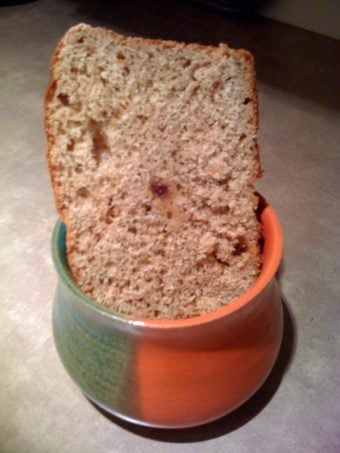 A slice ofOrange Raisin Whole Wheat Bread in an orange and green pot