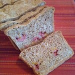 A loaf of mango and raspberry wheat bread, cut into slices on a red background