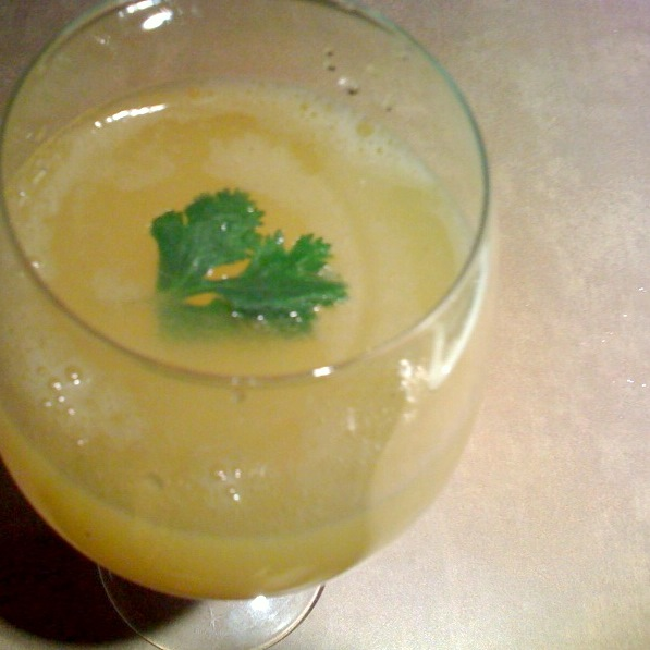 A top down shot of Aam Panna in a glass, garnished with a green herb