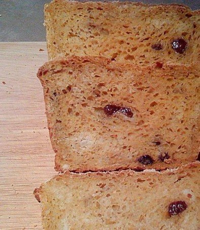 Slices of Carrot Ginger Raisin Bread on a wooden cutting board