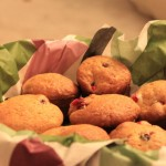 Spiced cranberry muffins in a cloth covered bowl