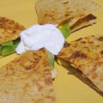 A grilled veggie quesadilla cut into quarters with sour cream in the centre. Placed on a yellow plate