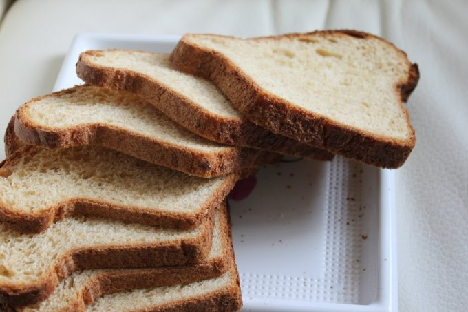 A pear carrot and oats bread loaf sliced on top of a white plate