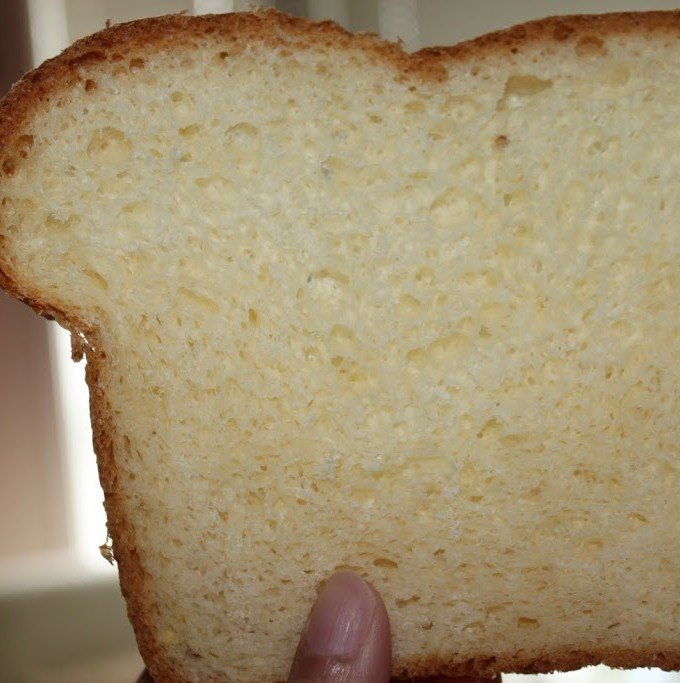 A slice of white sandwhich loaf being held towards the camera