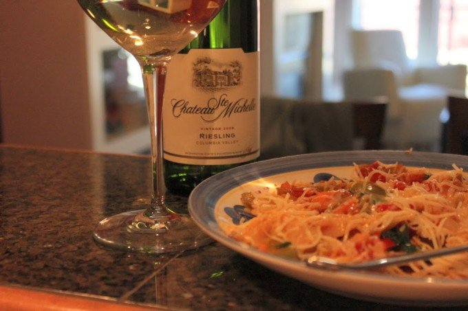 A quick farfalle served on a plate with a bottle of wine in the background