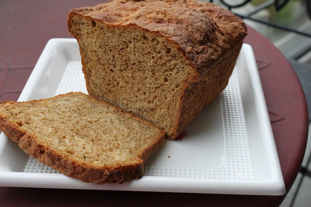 A loaf of greape oats flaxseed wheat bread on a white plate with the end sliced off