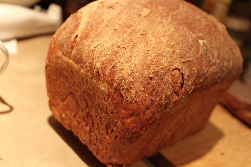 A loaf of Blueberry Apple Wheat Bread on a wooden chopping board