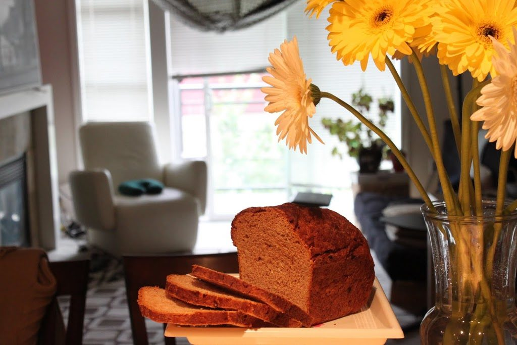 A loaf of date maple wheat bread cut into slices next to a bunch of flowers