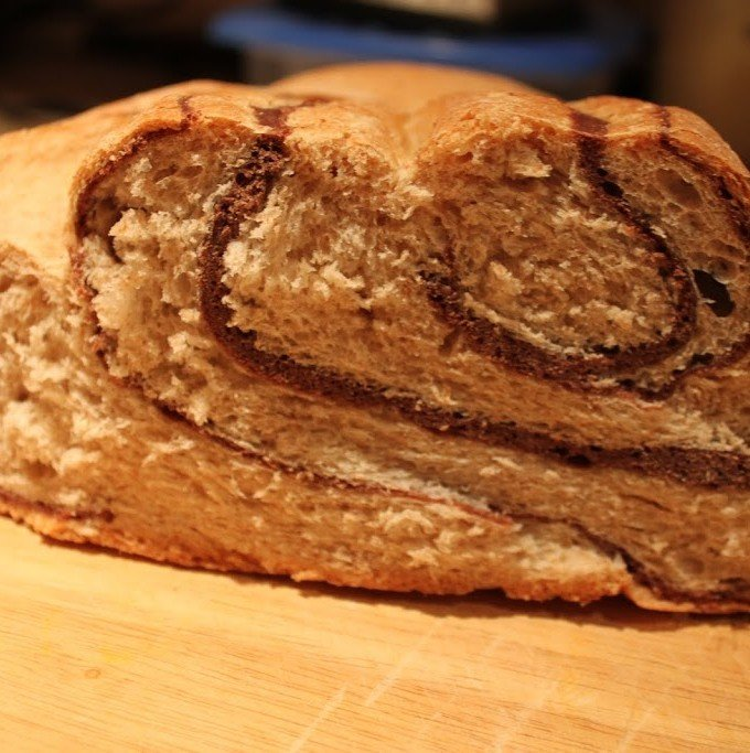 A loaf of chocolate swirl bread cut in half on a work surface