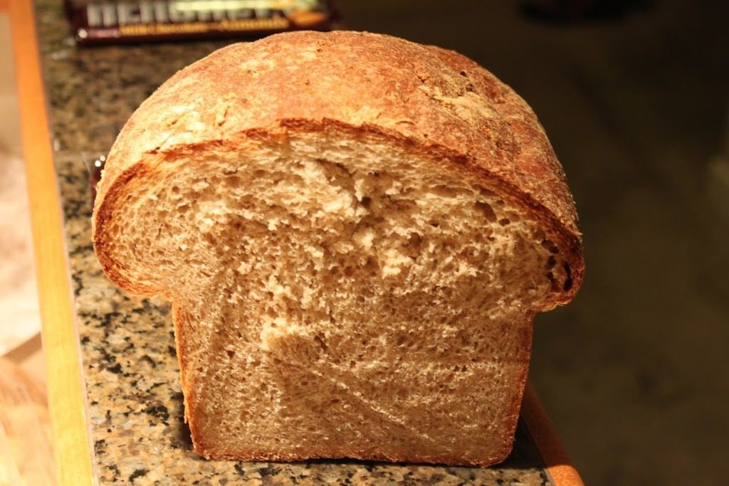 A loaf of wheat oat flax bread cut in half on a work surface