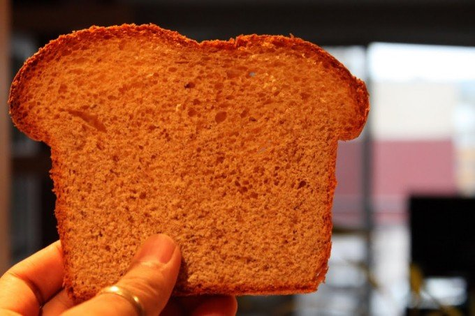 A slice of bread being held up towards camera