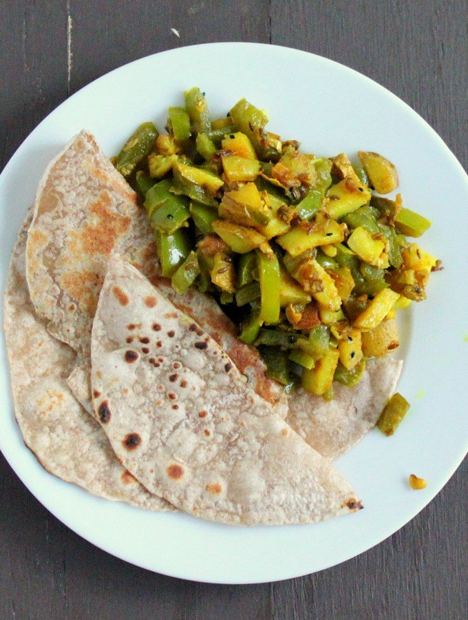 Saunf Aur Kalonji Waale Aloo Shimla Mirch served on a white plate with roti