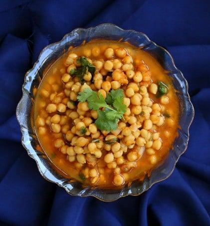 Imli chole served in a bowl on a dark blue background