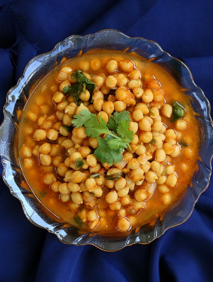 Imli chole served in a bowl on a dark blue background