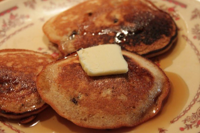 Ginger pancakes served on a white plate with a pat of butter