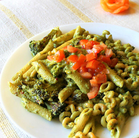 Basil cashew pesto with penne served on a white plate