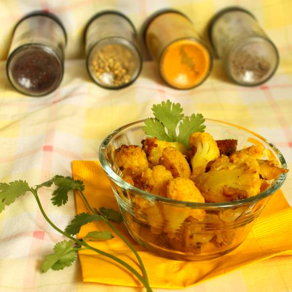 Gobi Aloo in a glass bowl next to spices