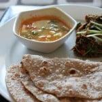 Baingan Bharta, sambhar, roti and papad sweved together on a white plate