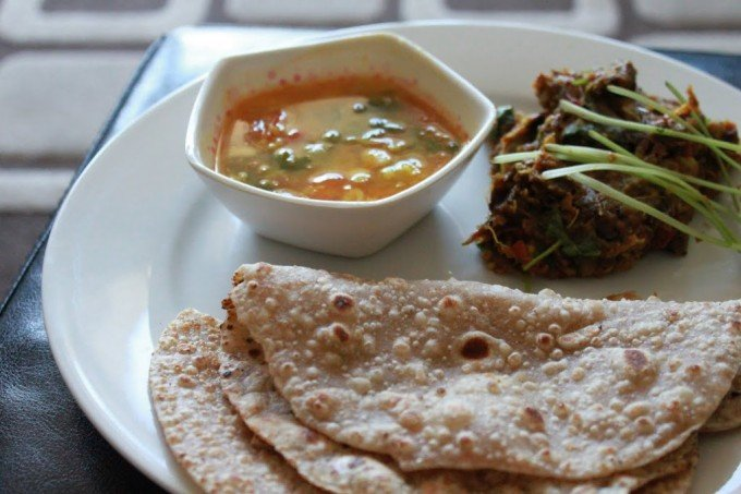 Baingan Bharta, sambhar, roti and papad sweved together on a white plate