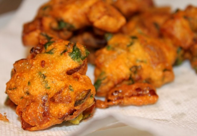 Onion fritters lying on some white parchment paper