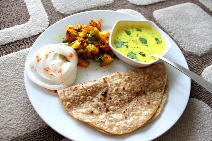 Tempered Cashew Yogurt, Spiced Potatoes and Bell Peppers with Indian Flat Bread served together on a white plate