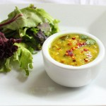 A small white bowl of yellow lentil soup served with salad