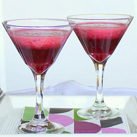 Two glasses of blueberry strawberry spiced cooler on a white background