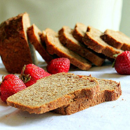 Slices of strawberry mango molasses loaf arranged with fresh strawberries