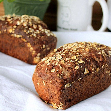 Two chocolate multigrain mini loaves on white fabric