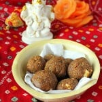 Besan laddoo in a pale bowl on a red background