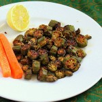 Crisp okra on a white plate werved with a lemon wedge and carrot sticks