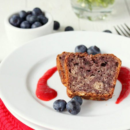 Two slices of blueberry Apple Whole Grain Cake served with fresh blueberries and a red sauce