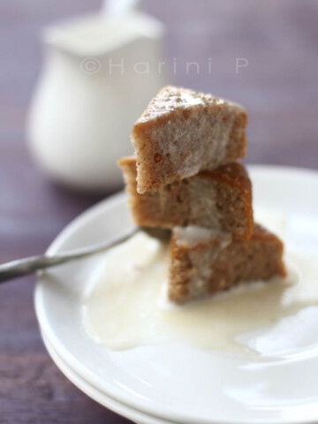 Pieces of gluten free carrot cake stacked on a white plate