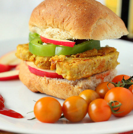 A tempeh frutter in a burger bun served with cherry tomatoes
