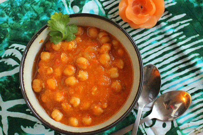 A bowl of vegan Chana Masala on a green cloth, garnished with cilantro