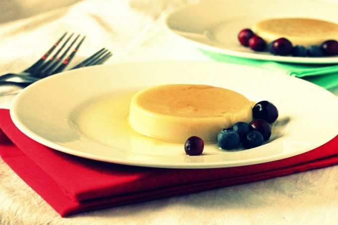 A caramel custard pudding on a white plate served with blueberries