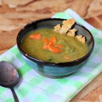 A bowl of Carrot Celery Leek Potato Soup on top of a checked green cloth