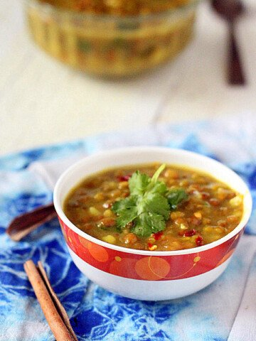 Mung bean daal soup served in a white and red bowl