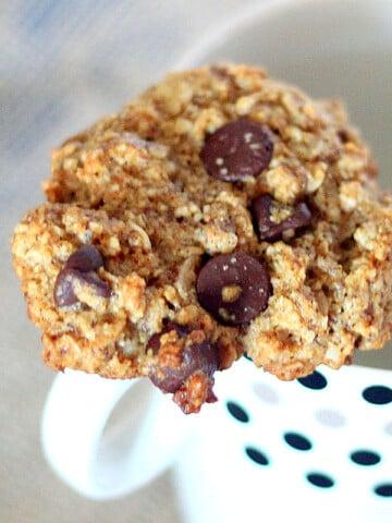 Oatmeal chocolate chip cookie resting on a mug