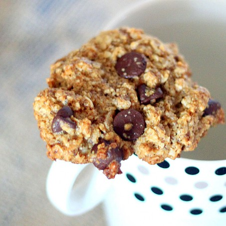 Oatmeal chocolate chip cookie resting on a mug