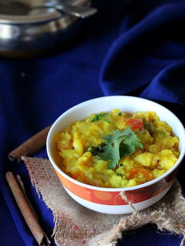 A yellow lentil stew in a bowl on a dark blue background
