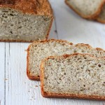 Pear Quinoa Chai spice Bread loaf with slices cut on a white wooden background.