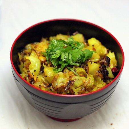A dark bowl of patta gobi sabzi on a marble countertop