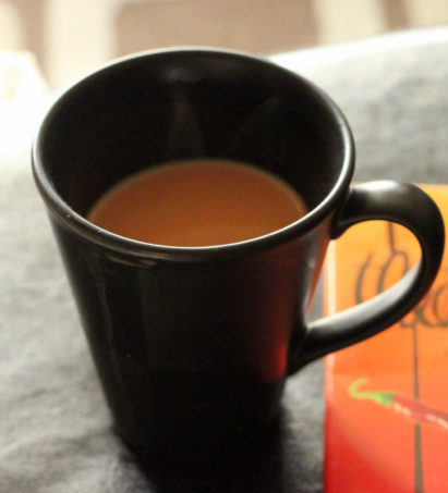 Indian Chai Tea in a black mug on a grey work surface