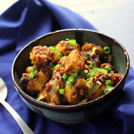 Keralan Tempeh Chili Roast in a black bowl on a blue cloth