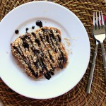 A slice of french toast on a white plate, drizzled with chocolate