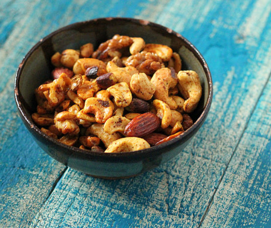 A bowl of spiced roasted nuts on a blue wood background
