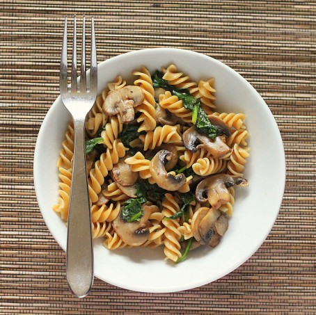 Mushroom fusilli in a white bowl with a fork. On a bamboo mat