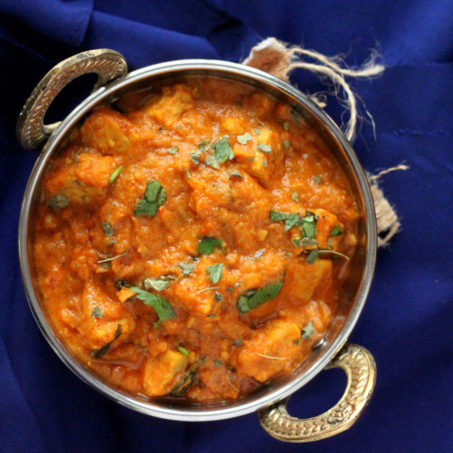 Paneer butter masala served in a siver dish, on a blue background